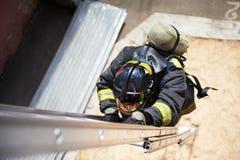 Escalada do sapador-bombeiro em escadas do incêndio Imagem de Stock