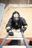 Escalada do sapador-bombeiro em escadas do incêndio Foto de Stock Royalty Free