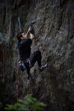 Escalada extrema do esporte Montanhista de rocha masculino novo em uma parede da rocha Imagens de Stock