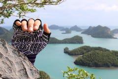 Escalada, manos con los guantes en la montaña Imagen de archivo libre de regalías
