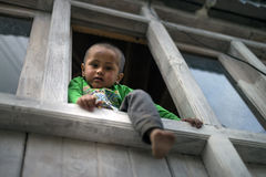 A escalada nova adorável e brincalhão do menino e senta-se na borda da janela da casa, olhando para baixo e no pé colado para for Fotos de Stock Royalty Free