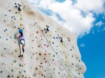 Escalada practicante de la mujer atlética asiática en una pared de la roca, actividad al aire libre con el fondo del cielo azul,  fotos de archivo libres de regalías