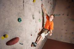 Escalada practicante del escalador masculino en una pared de la roca dentro Fotografía de archivo