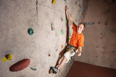 Escalada praticando do montanhista masculino em uma parede da rocha dentro Fotografia de Stock