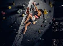 Escalada praticando vestindo do sportswear da jovem mulher em uma parede dentro foto de stock