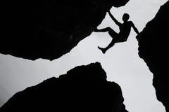 Escalada, subida del hombre entre la roca tres en el acantilado Imágenes de archivo libres de regalías