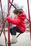 Escaladas da menina da criança de 5 anos em uma estrutura do ferro imagens de stock