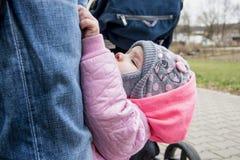 Escaladas da menina na calças do paizinho, foto bonita de uma criança que queira obter sobre suas mãos imagem de stock royalty free