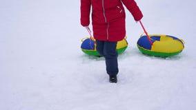 Escaladas da menina na montanha nevado alta que guarda pires da neve Jogos das crianças com os trenós no inverno Resort de montan filme