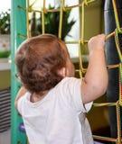 escaladas do bebê de 9 meses na rede fotografia de stock royalty free