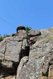 Escaladas do montanhista de rocha da menina em uma rocha foto de stock