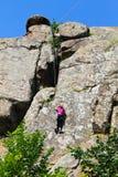 Escaladas do montanhista de rocha da menina na rocha fotos de stock