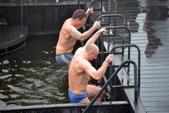 Escaladas dos homens fora da água gelada Fotografia de Stock Royalty Free