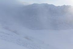 Escaladez les montagnes dans une tempête de neige Photos stock