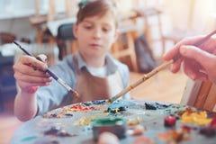 Escalado acima do olhar em pinturas de mistura da criança na paleta Foto de Stock Royalty Free