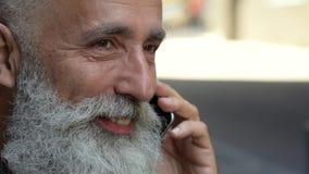Escalado encima de mirada en el hombre barbudo que habla en el teléfono almacen de video