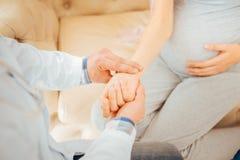 Escalado encima de mirada en el médico que comprueba pulso de la mujer embarazada fotografía de archivo
