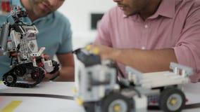 Escalado encima de mirada en los ingenieros de sexo masculino que charlan sobre el robot almacen de video