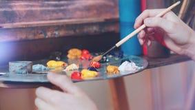 Escalado encima del tiro de la mano del niño que mezcla las pinturas coloridas Fotografía de archivo