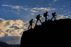 Escalador acertado y caminar la silueta del grupo Fotografía de archivo libre de regalías