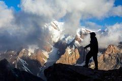 Escalador alpino que alcanza la cumbre Fotos de archivo libres de regalías