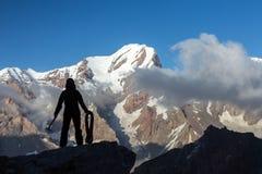 Escalador alpino que arregla pendiente con el hacha de la cuerda y de hielo Foto de archivo libre de regalías