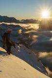 Escalador con la opinión hermosa de la puesta del sol de la montaña Fotos de archivo