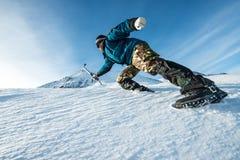 Escalador con una subida del hacha de hielo en la montaña nevosa imágenes de archivo libres de regalías