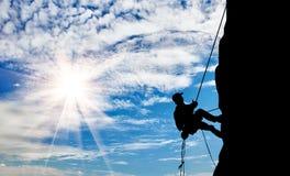 Escalador de la silueta que sube una montaña Imagenes de archivo