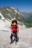 Escalador de montaña con el hielo-hacha Imagenes de archivo