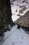 Escalador de montaña masculino en una reguera muy escarpada y estrecha en una cuerda y la mirada abajo Imagenes de archivo