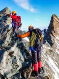 Escalador de montaña masculino y femenino en un canto rocoso expuesto de la cumbre en su manera a un alto pico de montaña alpino foto de archivo