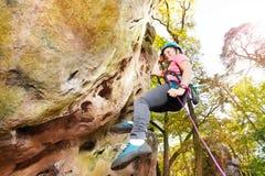 Escalador de roca adolescente que ejercita en el día soleado Imágenes de archivo libres de regalías