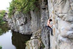 Escalador de roca en un acantilado sobre un río de la barranca Imagenes de archivo