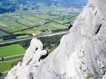 Escalador de roca en un risco que sube escarpado y expuesto de la piedra caliza en las montañas suizas sobre campos verdes enorme fotos de archivo libres de regalías