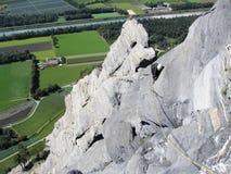 Escalador de roca en un risco que sube escarpado y expuesto de la piedra caliza en las montañas suizas sobre campos verdes enorme fotografía de archivo libre de regalías
