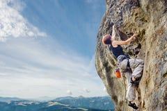 Escalador de roca femenino en el acantilado sobresaliente escarpado de la roca Imagenes de archivo