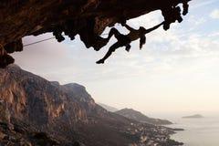 Escalador de roca femenino en la puesta del sol Imagen de archivo
