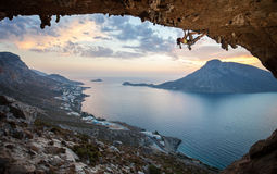 Escalador de roca femenino en la puesta del sol imagen de archivo libre de regalías