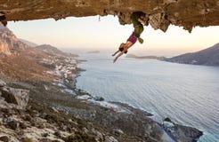Escalador de roca femenino que descansa mientras que cuelga al revés en la ruta estimulante en cueva en la puesta del sol imagen de archivo libre de regalías