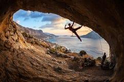 Escalador de roca femenino que presenta mientras que sube Fotografía de archivo