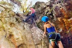 Escalador de roca joven que alcanza la cumbre de la montaña foto de archivo