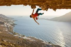 Escalador de roca masculino en la ruta estimulante que va a lo largo de techo en cueva imagen de archivo