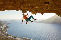 Escalador de roca masculino en la ruta estimulante que va a lo largo de techo en cueva foto de archivo