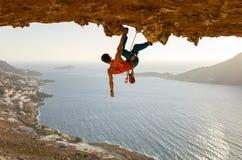 Escalador de roca masculino en la ruta estimulante que va a lo largo de techo en cueva fotografía de archivo libre de regalías