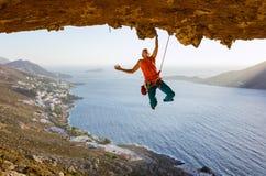 Escalador de roca masculino en la ruta estimulante que va a lo largo de techo en cueva imágenes de archivo libres de regalías