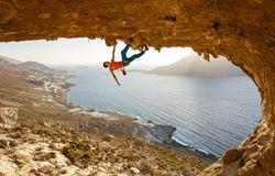 Escalador de roca masculino en la ruta estimulante que va a lo largo de techo en cueva fotos de archivo