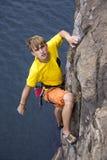 Escalador de roca masculino joven que cuelga sobre el agua Imágenes de archivo libres de regalías