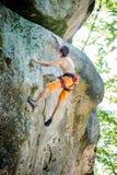 Escalador de roca masculino que sube con la cuerda en una pared rocosa foto de archivo libre de regalías