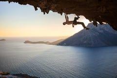 Escalador de roca masculino que sube a lo largo de un tejado en una cueva Fotos de archivo libres de regalías